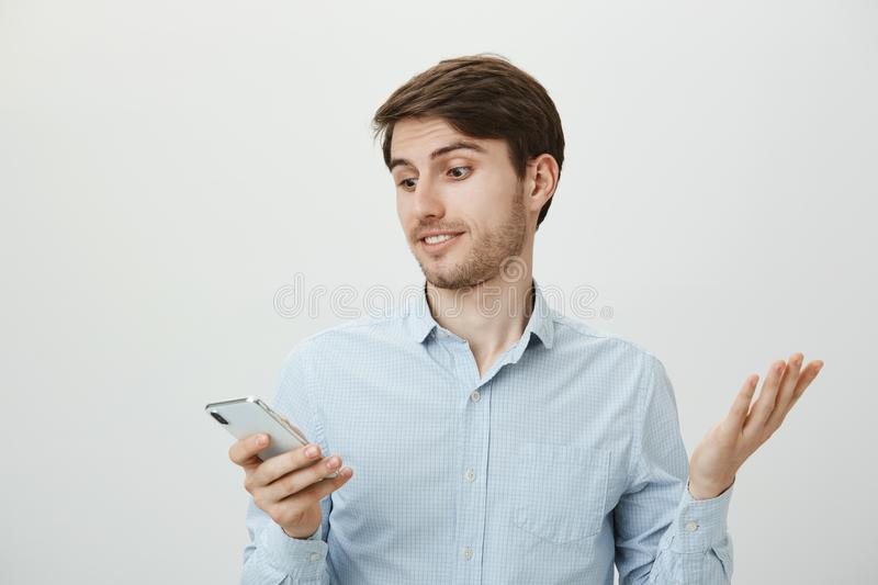 What the hell does it mean. Questioned and clueless positive handsome guy in blue shirt shrugging, raising palm in. Confusion and looking at screen of royalty free stock photography