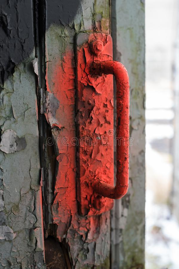 What is hiding behind the old gate with the red handle stock photo