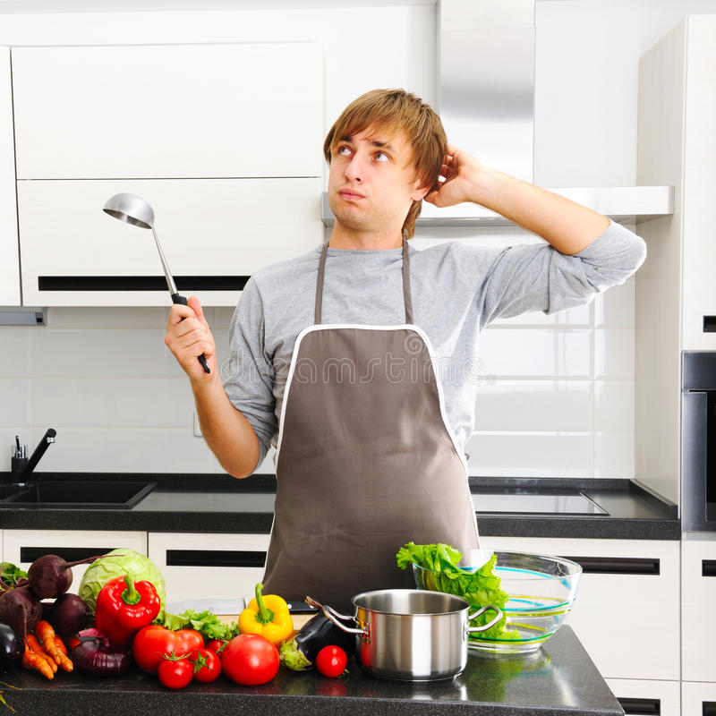 What am I cooking?. Man cooking in modern kitchen stock images