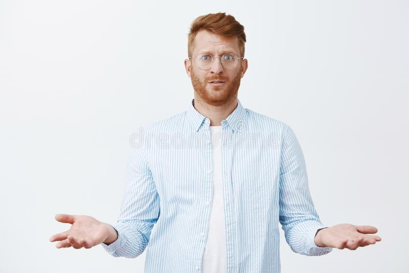 What I did wrong. Confused gloomy handsome redhead guy with beard in glasses and shirt, standing with questioned royalty free stock photo