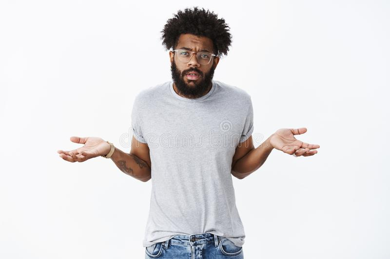 So what, I not care. Portrait of unbothered, indifferent confident african american man with beard and curly hair. Shrugging with hands spread sideways in stock image