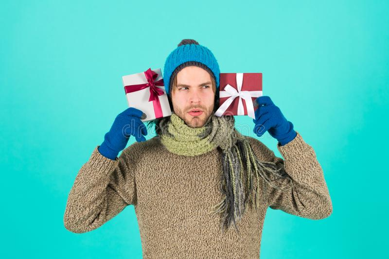 What is inside. Man bearded handsome wear winter hat scarf gloves hold two gift boxes. Hipster hold christmas gift with stock photo