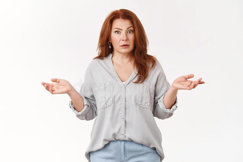 What just hapenned. Confused clueless middle-aged redhead woman shrugging hands spread sideways perplexed express full stock image