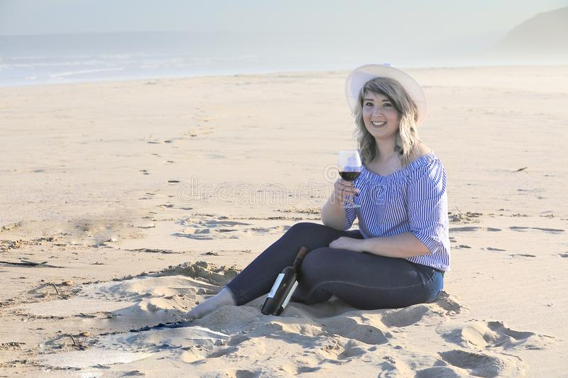 What a lovely glass of red wine. A lovely lady is relaxing on a sunny spring afternoon at Kleinbrak on the Garden Route of South Africa with a glass of red wine stock photo