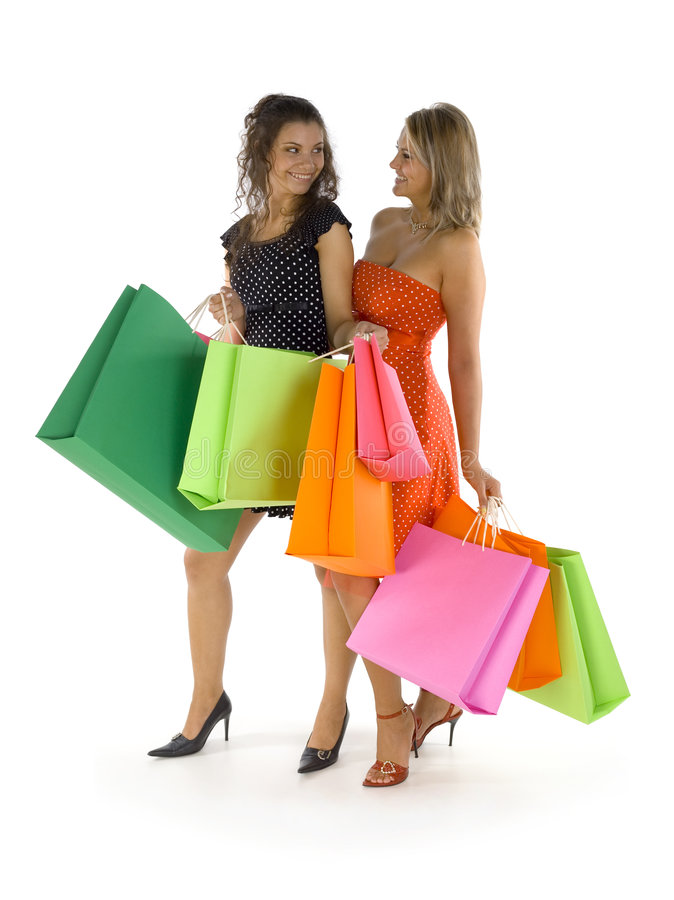 What now?. Two beautiful, young woman standing and holding bags. First woman is showing something in her's bag. Both woman are looking at each other. Isolated on royalty free stock photo