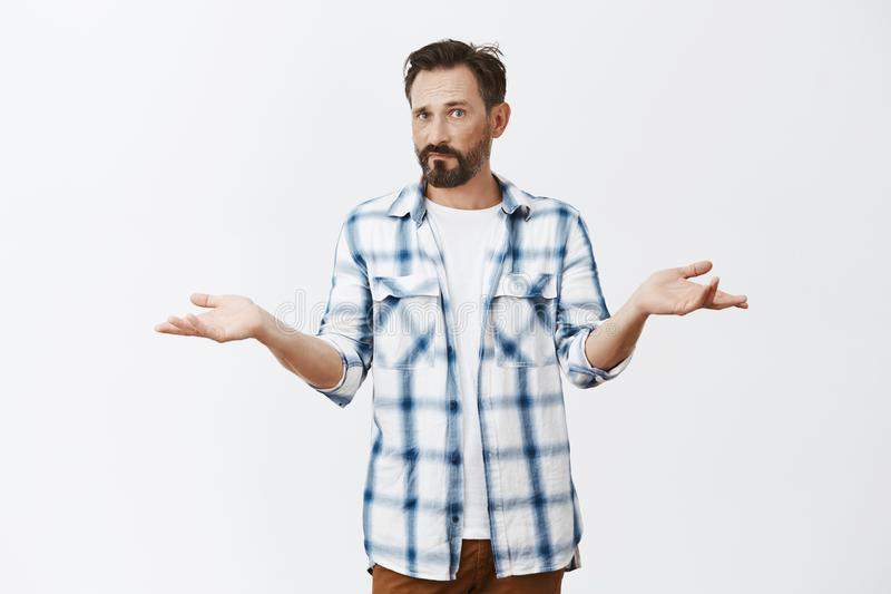 So what is our problem. Confused and puzzled handsome mature caucasian man with beard and moustache, standing with. Spread hands in clueless pose, feeling royalty free stock photos