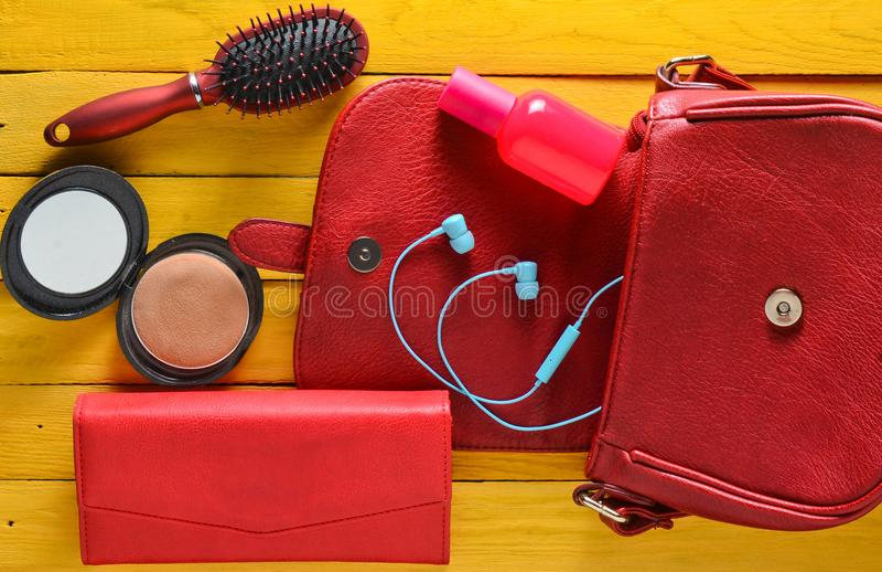 What& x27; s nel women& x27; borsa di s? Una borsa rossa, borsa di cuoio, cuffie, specchio, pettine, bottiglia di profumo su una  fotografia stock
