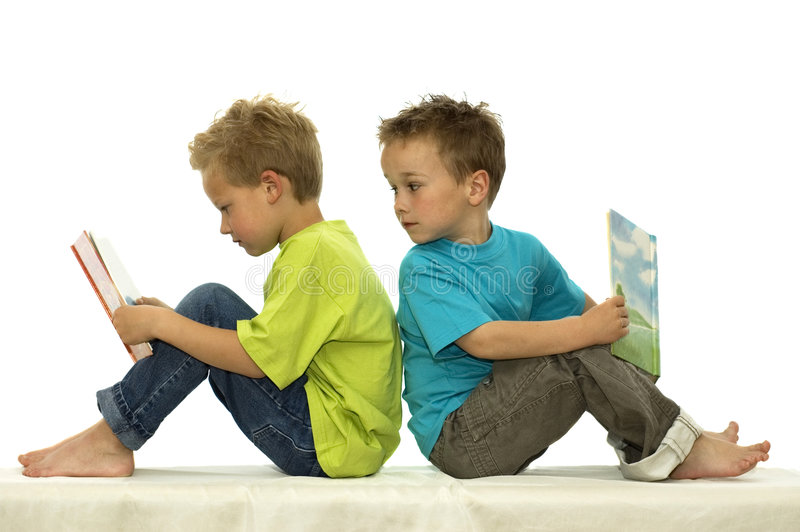 What's he Reading. Two friends reading a book, one boy looking surprised at the book of the other