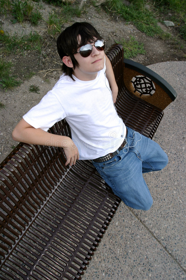 What's Up?. Male teenager in blue jeans, white t-shirt and big sunglasses. Ear buds from an MP3 player visible. Sitting on a park bench ready to deliver your stock photo