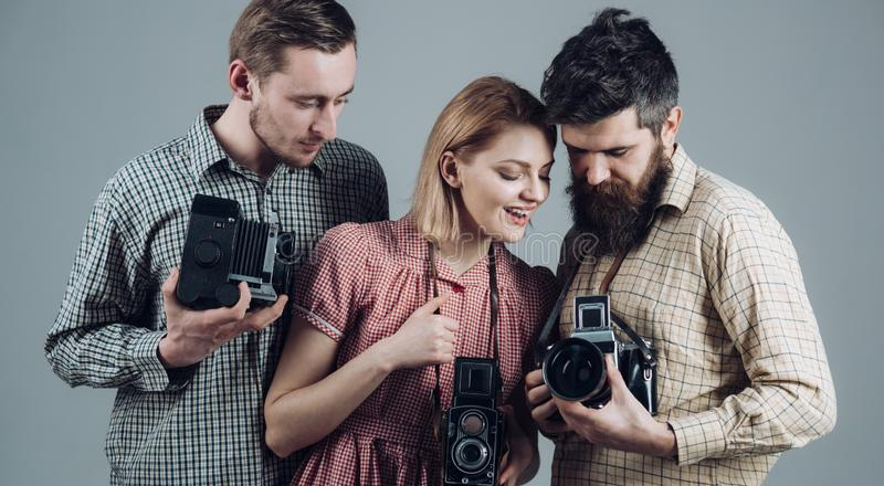 What a shot. Photography studio. Retro style woman and men hold analog photo cameras. Paparazzi or photojournalists with stock image