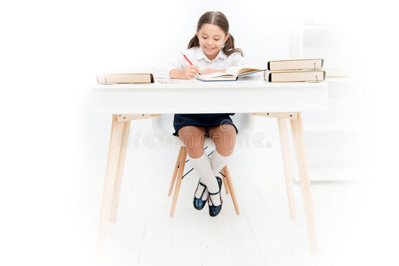 What should be height of study table. Schoolgirl doing homework at table. Adorable pupil little girl studying at table. White background. Studying on desk with stock photos