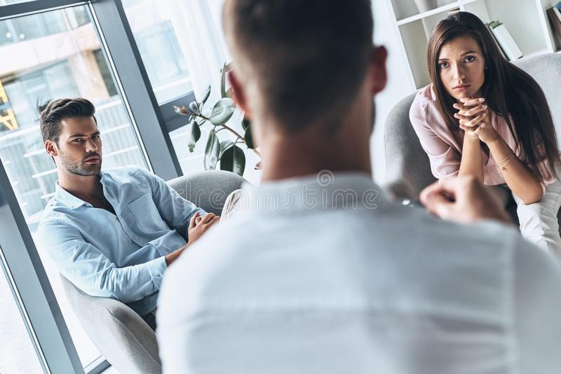 What should we do?. Young married couple looking at psychologist while sitting on the therapy session stock photo