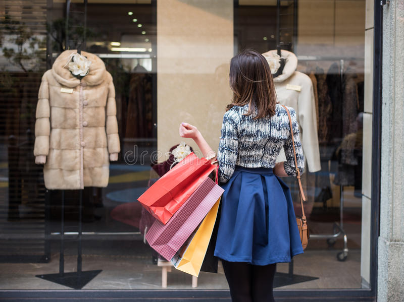 What should I buy. Beautiful brunette girl holding big colorful shopping bags in front of a window of a store in the city mall, Looking at modern fashion and stock photo