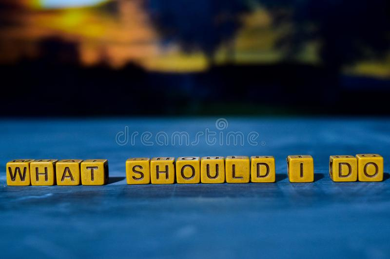 What should I do? on wooden blocks. Cross processed image with bokeh background royalty free stock photos