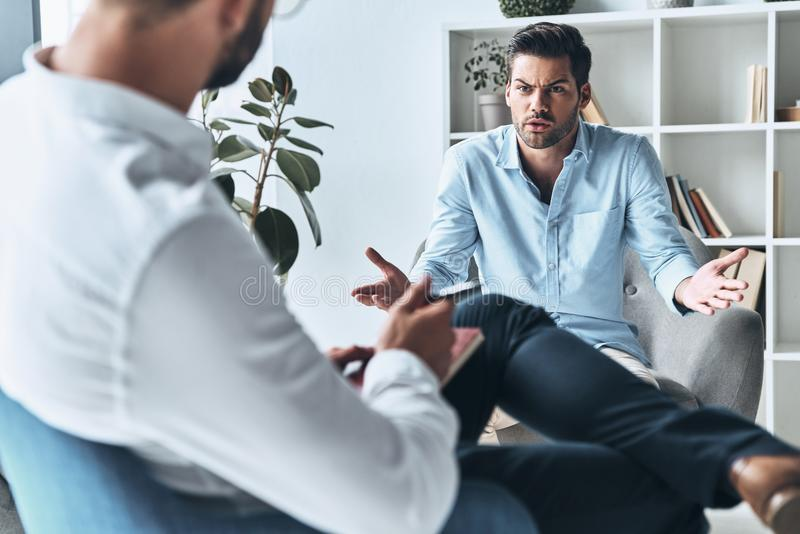 What should I do?. Young frustrated men speaking and gesturing while sitting on the therapy session with psychologist royalty free stock photos