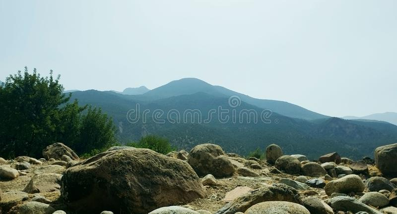 Nature of the Mountain. What smooth stones like that of the valley and the green pine tree lying alone on the edge of the cliff overlooking the hills and gray royalty free stock photo