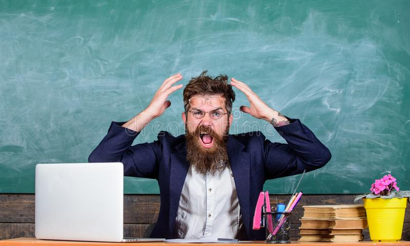 What stupid thought. Man bearded teacher aggressive expression sit classroom chalkboard background. Unpleasant wonder royalty free stock photos
