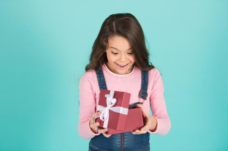 What a surprise. Child surprised excited holds gift box turquoise background. Kid girl surprised gift. Girl curly royalty free stock photo