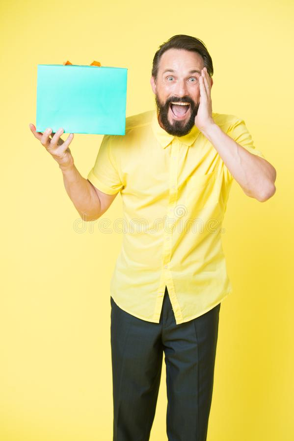 What a surprise. Man mature bearded guy surprised face holds gift box. Man got unexpectable gift. Guy surprised by gift. Yellow background. Presents make our royalty free stock photography