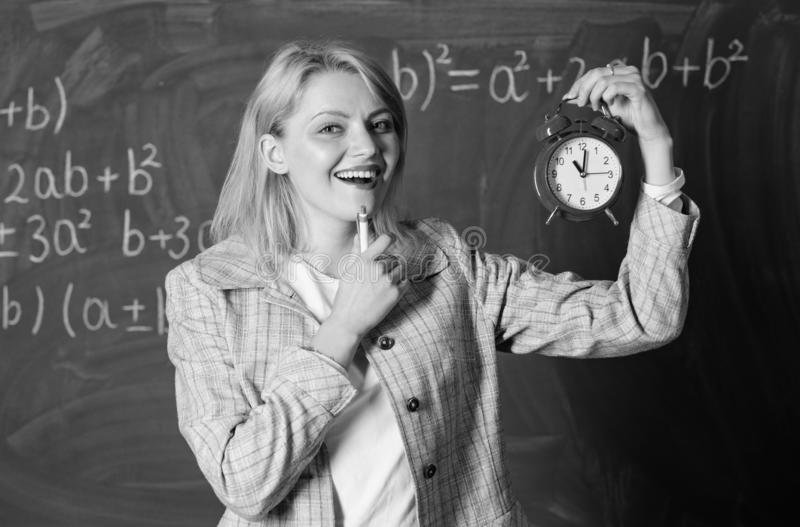 What time is it. Woman teacher hold alarm clock. Girl formal wear school lecturer. Time to study. Welcome teacher school royalty free stock image