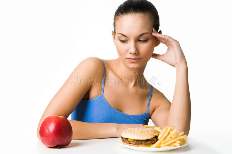 What to choose?. Portrait of pretty young girl deciding what to eat: an apple or hamburger with fried potatoes royalty free stock photo