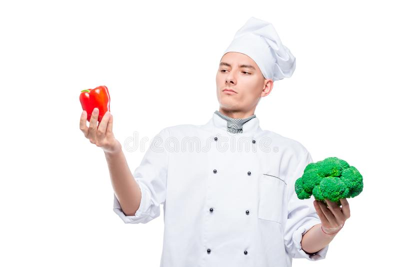 What to choose - pepper or broccoli - concept portrait of a cook with vegetables on a white royalty free stock photo