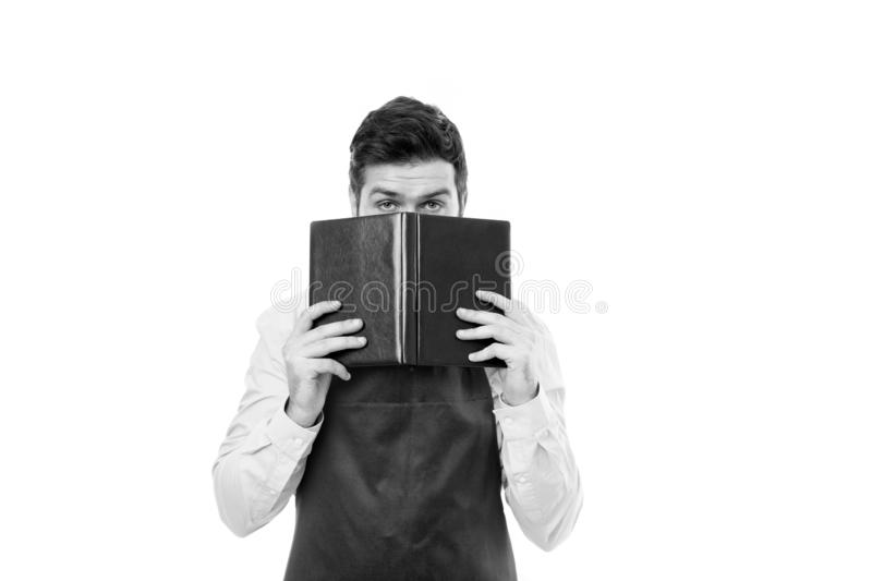 What to cook. Man hipster cook apron reading book about culinary. No idea how cook food. Culinary book concept. Man in stock photo