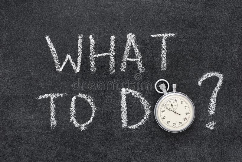 What to do. Question handwritten on chalkboard with vintage precise stopwatch used instead of O royalty free stock photography