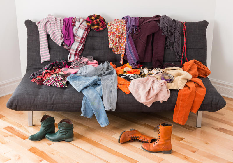 What to wear?. Messy colorful clothing on a sofa royalty free stock photo