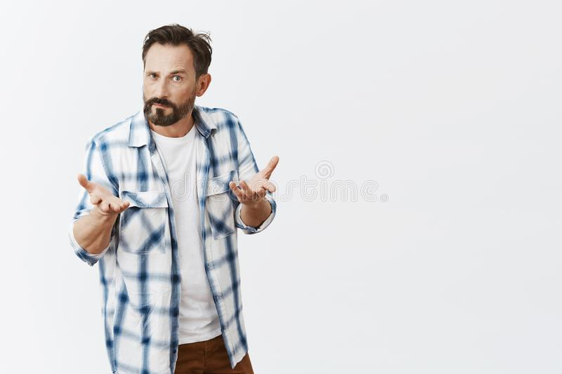 What is tour point, I am mad. Annoyed and adult husband with beard and moustache, gesturing with raised palms. Pursing lips and staring with angry and scary stock image