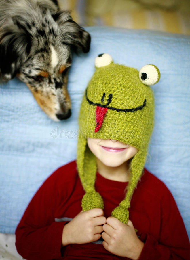 What in the World??. Comical photo of a child wearing a frog hat with a curious dog trying to figure out what it is