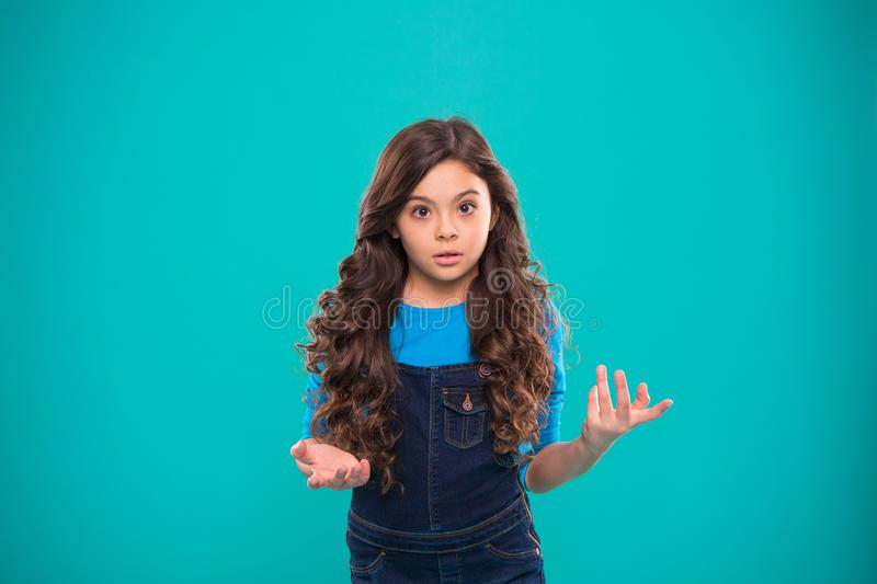 What are you talking about. Kid stunned bewildered emotion can not believe her eyes. Girl curly hairstyle wondering. Child bewildered stunned face blue stock photography
