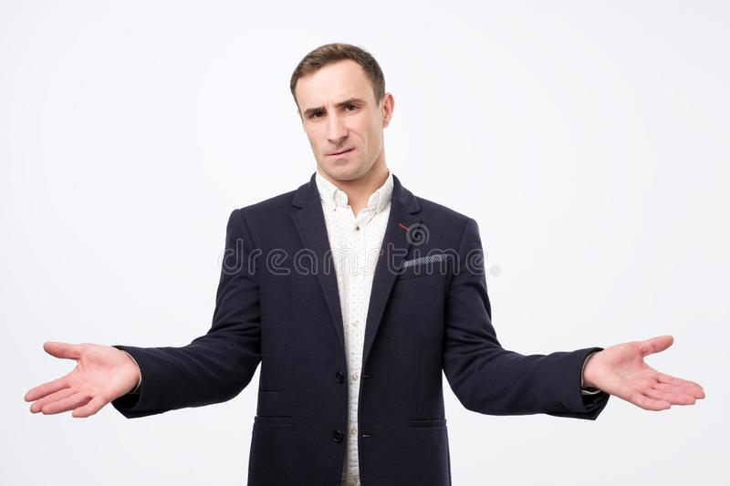 Man on grey background being at a loss, showing helpless gesture with arm and hands stock photo