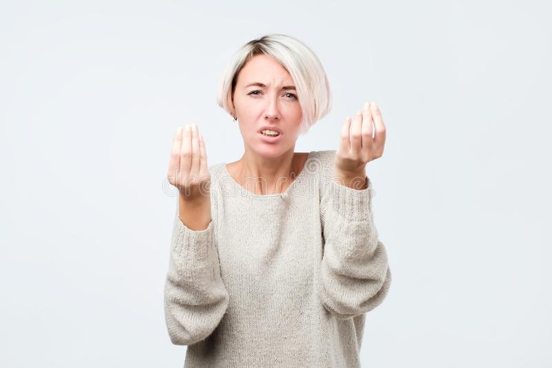 What is your point. Woman frowning and showing italian gesture with han stock photo