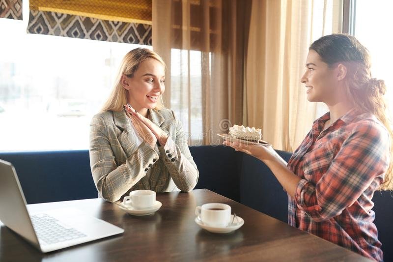 What a yum. Happy brunette women holding plate with yummy cake while her friend of colleague looking at it excitedly stock photos