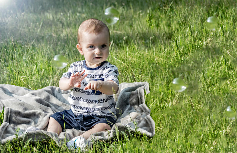 whatching在飞行肥皂泡和开会的逗人喜爱的惊奇的男婴在绿草夏天晴天 免版税库存图片