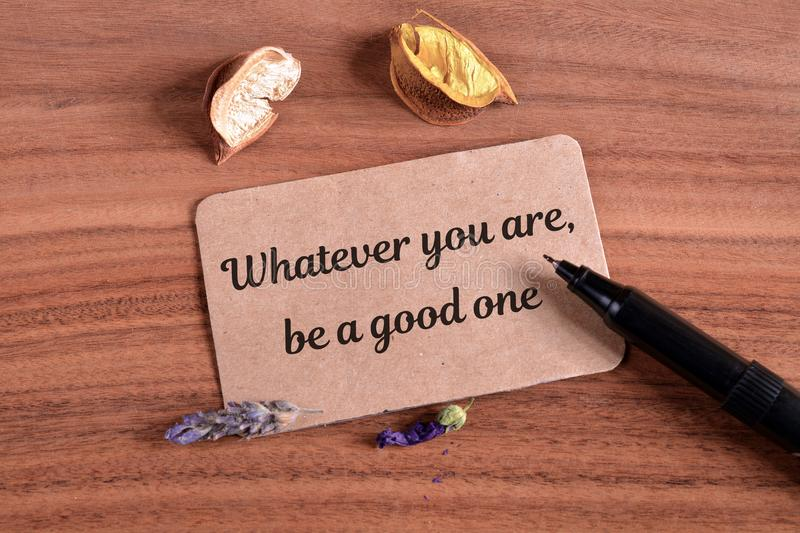 Whatever you are be a good one. Text write in card on wood stock image