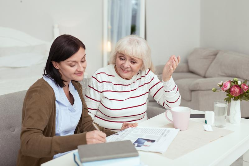 Pleasant elder woman and caregiver inspecting newspaper. Whats new. Optimistic elder women and caregiver reading news and talking stock photo