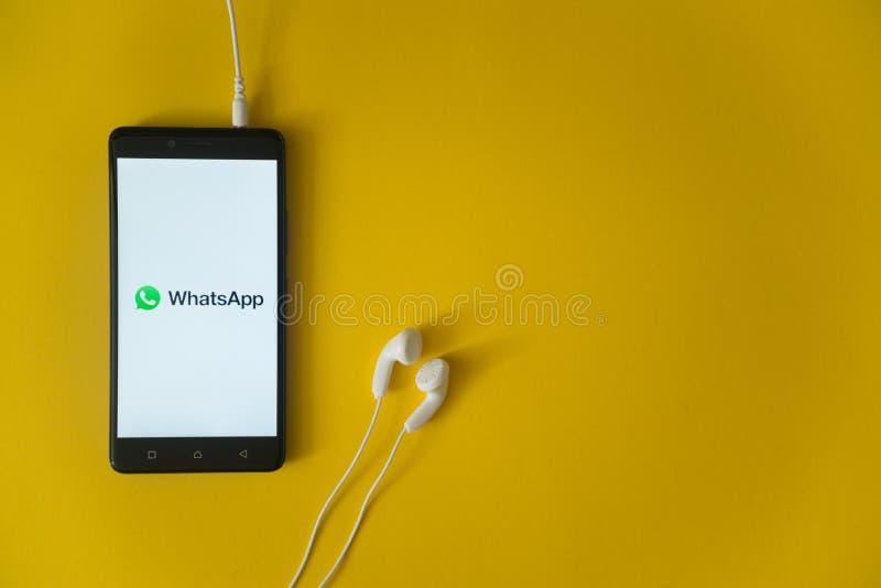 Whatsappembleem op het smartphonescherm op gele achtergrond stock foto