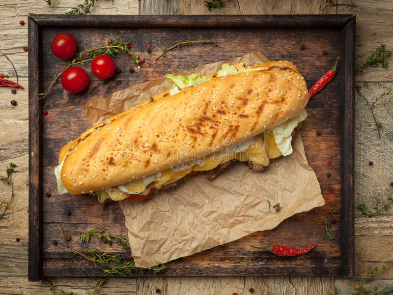 Wheat baguette, beef tenderloin, grilled royal cheese, tomato, i. Wheat baguette with sesame seeds, slices of beef tenderloin, grilled royal cheese, tomato royalty free stock images
