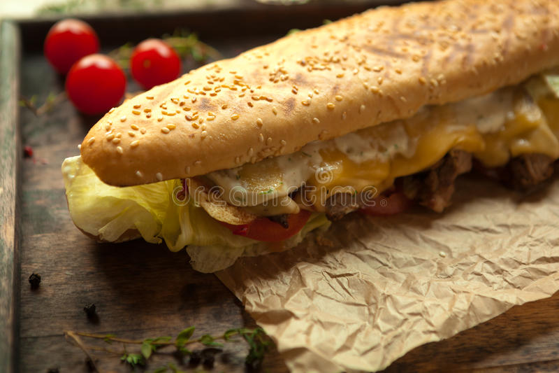 Wheat baguette, beef tenderloin, grilled royal cheese, tomato, i. Wheat baguette with sesame seeds, slices of beef tenderloin, grilled royal cheese, tomato stock photography