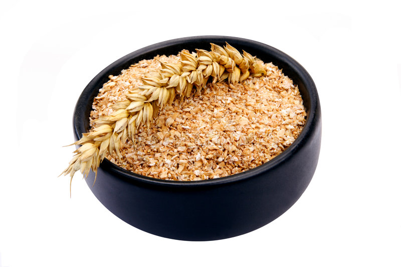 Wheat bran. Bowl of wheat bran with wheats ear on white background. It is common ingredient of healthy meal royalty free stock photos