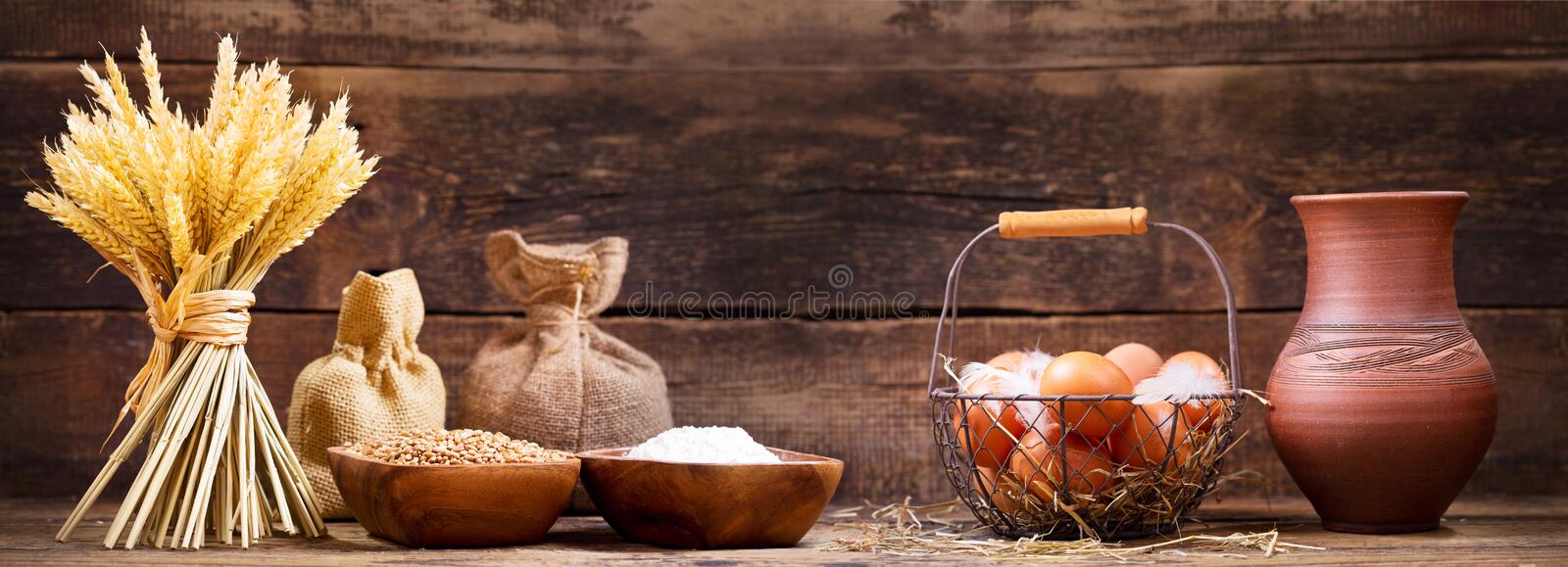Wheat ears with bowl of grains, flour, milk and eggs royalty free stock images