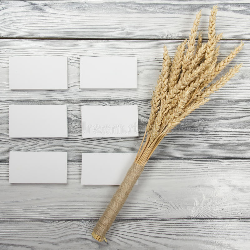 Wheat Ears on Wooden Table with blank business cards. Sheaf of Wheat over Wood Background. Harvest concept. Wheat Ears on Wooden Table with blank business cards stock image