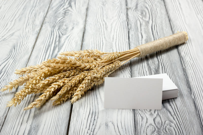 Wheat Ears on Wooden Table with blank business cards. Sheaf of Wheat over Wood Background. Harvest concept. Wheat Ears on Wooden Table with blank business cards stock photography