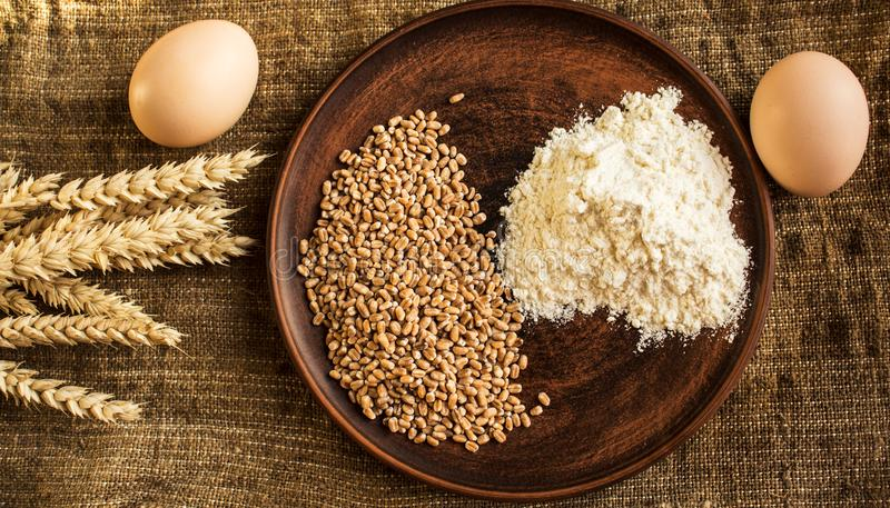 Wheat flour eggs and spikelets of wheat on sackcloth background royalty free stock image