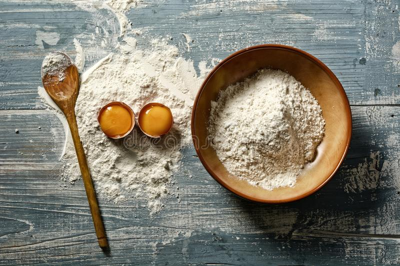Wheat flour and eggs on wooden table - horizontal. Closeup stock image