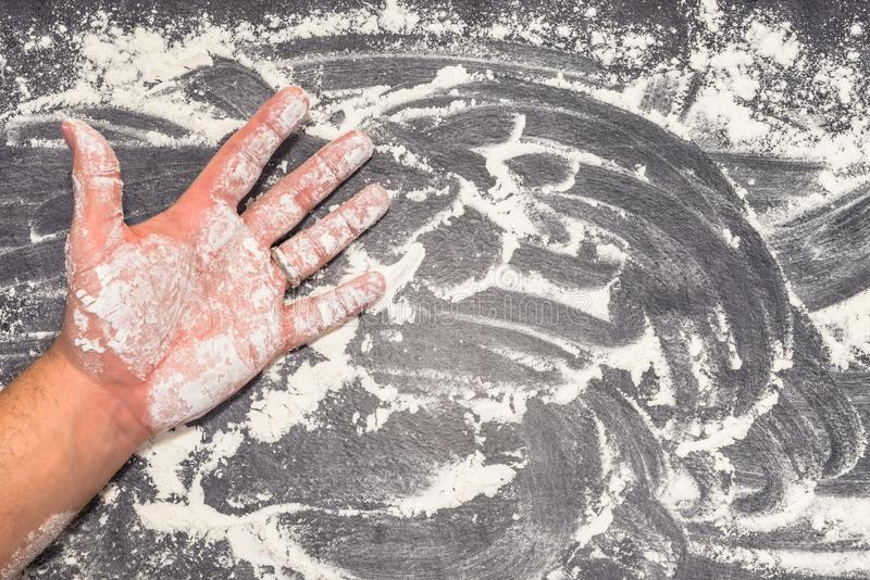 Wheat flour on grey working surface with male hand.  royalty free stock photos
