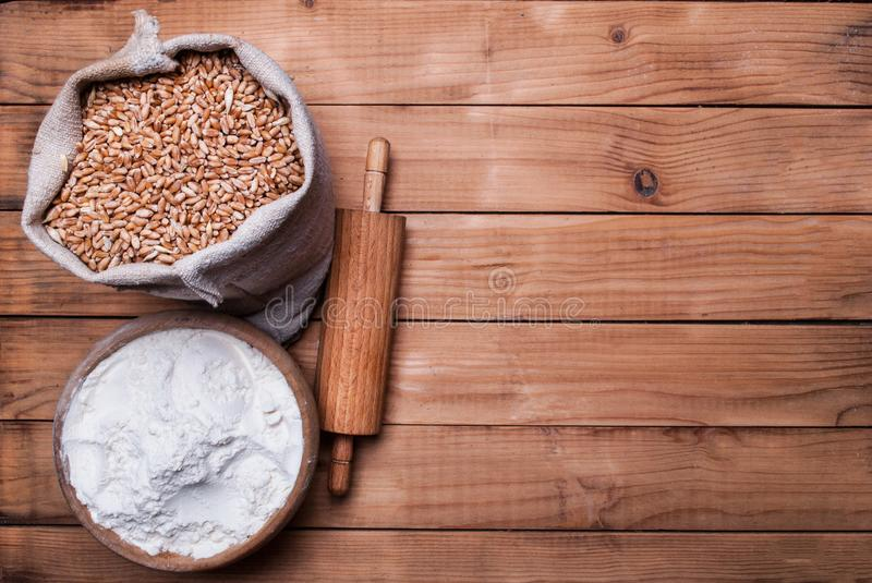 Wheat grains in burlap bag and white flour in bowl and rolling pin on wooden desk royalty free stock photos