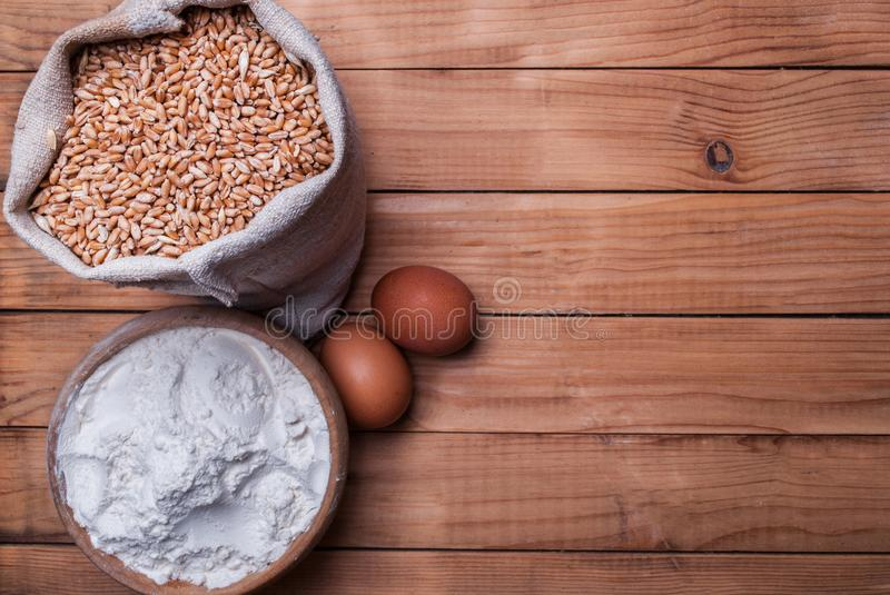 Wheat grains, flour in bowl and eggs on wooden desk with space for text royalty free stock photo